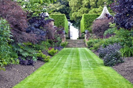 Elegant, traditional landscaped garden with lush green lawn