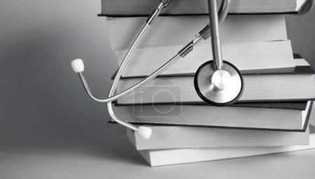 Stethoscope on pile of books isolated. Blue backgr...