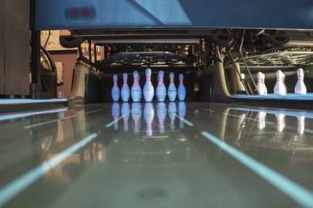 White skittles for bowling and their reflection