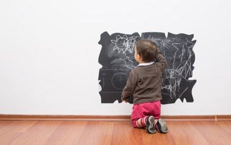 Photo pour Petite fille dessin sur le mur - image libre de droit