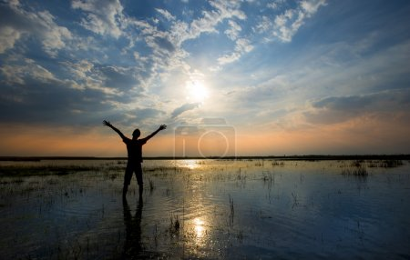 Man holding arms up in praise in sunset  while being in water