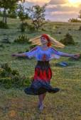 Beautiful blonde woman in old-fashioned dress dancing at sunset