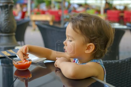 Photo for Little girl playing with ketchup at restaurant - Royalty Free Image