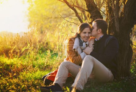 Photo for Young couple sitting and kissing near the tree in the forest - Royalty Free Image