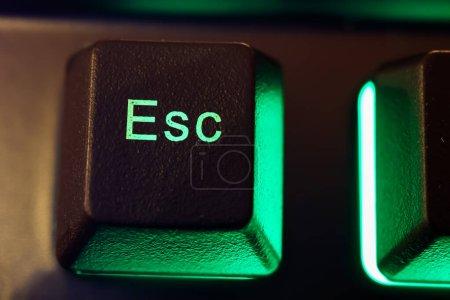 Makro primer plano de la tecla esc iluminada verde aislada en el teclado de la computadora (enfoque en la letra S)
