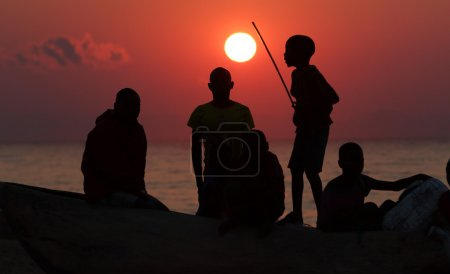 A group of fishermen and kids at sunrise,