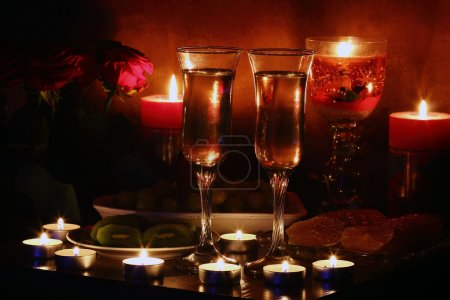 Photo pour Champagne, fruit, candles and a romantic evening - image libre de droit