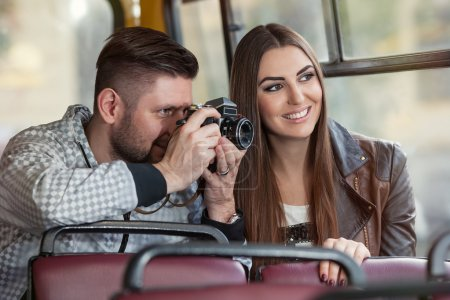 Photo for Two playful tourists taking fun photos from the bus on the film camera - Royalty Free Image