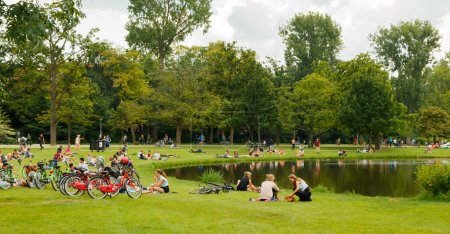 Photo pour Amsterdam, Pays-Bas - 5 août 2014 : Vondelpark un lieu de repos et de promenade préféré des résidents et des touristes. Les gens s'assoient, mangent, se rencontrent juste sur les pelouses - image libre de droit