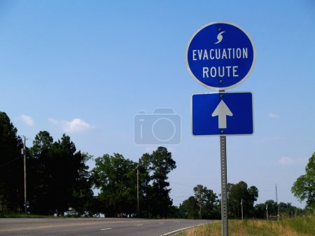 Blue hurricane evacuation route sign along a highway.