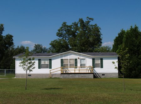 White single-wide mobile residential low income ho...