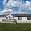 Gray trailer home with stone foundation or skirtin...