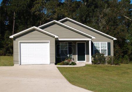 Une histoire résidentielle faible revenu à la maison avec bardage en vinyle gris et garage entrée avant