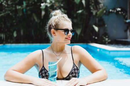 Woman posing in a pool of blue water