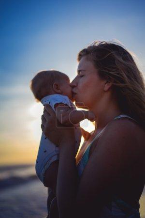 Photo pour Jeune femme avec son bébé sur la plage pendant le coucher du soleil. Mère avec son bébé sur la plage regardant le coucher du soleil . - image libre de droit