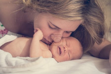 Mom gently kissisng newborn baby