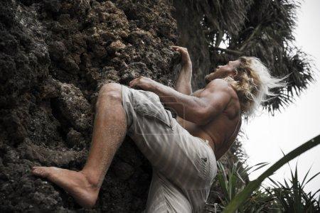 brutal man climbing up the rock