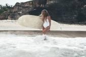 woman in bikini posing with surfboard