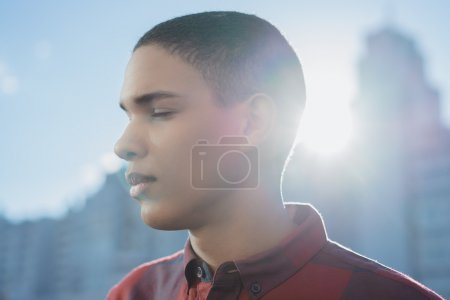 man standing with closed eyes in modern city