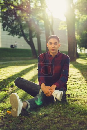 man sitting on grass at city park