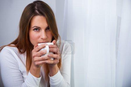 Photo pour Jeune femme assise sur une chaise près d'une fenêtre, sirotant une tasse chaude de thé, café, chocolat chaud ou soupe . - image libre de droit
