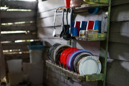 Photo pour Pauvre cuisine dans la maison de planches de bois usées. La cuisine ne contient que l'équipement le plus nécessaire comme des casseroles, assiettes, bols et verres. Misérable taudis grincheux - image libre de droit
