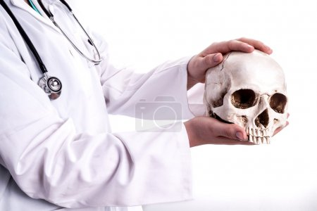 Doctor holding a skull in his hands.