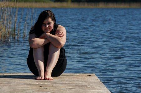 Photo pour Jeune femme assise méditant sur la jetée près du lac au soleil - image libre de droit