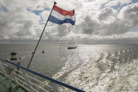 Photo pour Wadden Sea with Dutch flag as seen from the ferry from the town called Harlingen to the island Terschelling. - image libre de droit