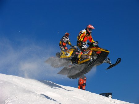 Snocross racers flying over a hill at the Duluth snocross race.