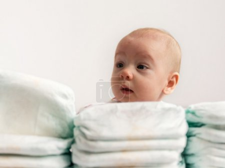 Baby looking over stack of diapers 2