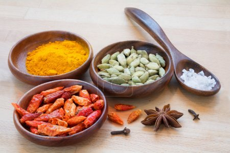 Colorful spices in a spoon an bowls from dark trop...