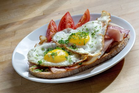 bread with ham and fried egg garnish with chives on a plate