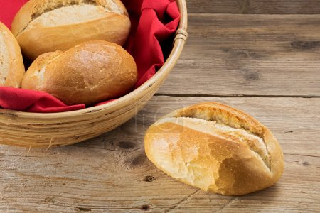 bun and bread rolls in a basket whith red napkin on old wood