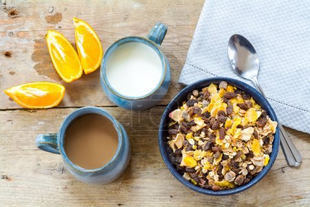 breakfast granola with milk, coffee and sliced oranges on a wea