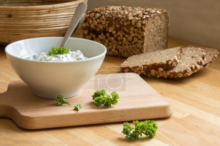 curd cheese dip with herbs in a bowl and rustic bread in the bac
