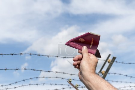 Man's hand holding a passport as a paper airplane over a barbed