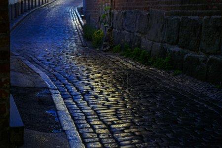 Straße mit feuchtem Kopfsteinpflaster in der Nacht in einer Altstadt