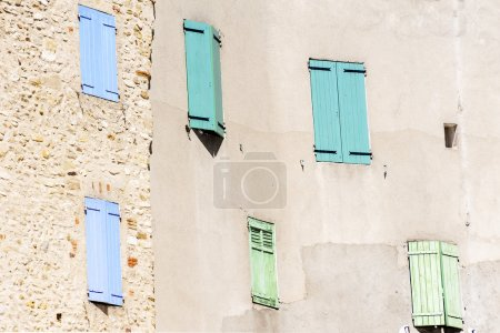 Photo for Facade with closed window shutters in blue, turquoise and green in an old town in South Europe, France - Royalty Free Image