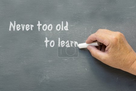 older hand writes on a chalkboard: Never too old to learn