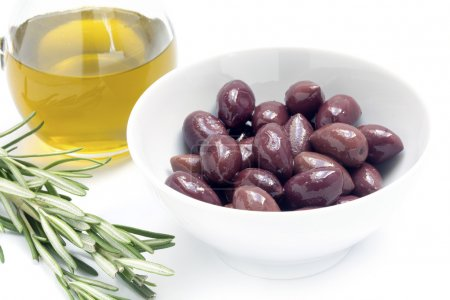 Kalamata black olives in a white bowl and olive oil, rosemary ga