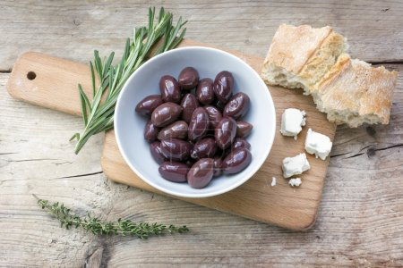 Kalamata black olives, bread, feta cheese and herbs on rustic wo