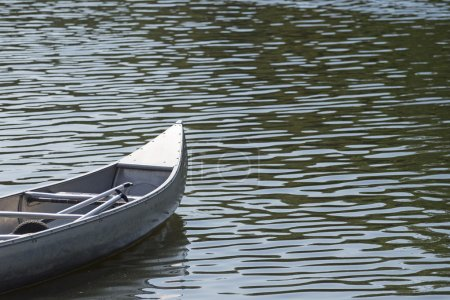 Prow of a canoe on the water with small glittering waves