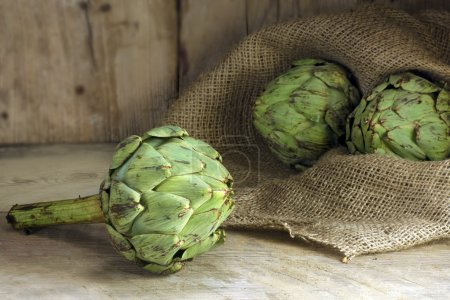 Natural artichokes on rustic wood