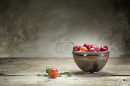 wild red plums in a pottery bowl on an old wooden table