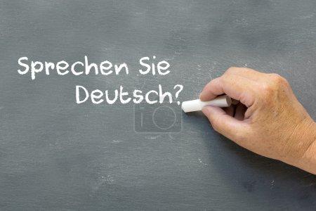 Hand on a chalkboard with the German words Sprechen Sie deutsch