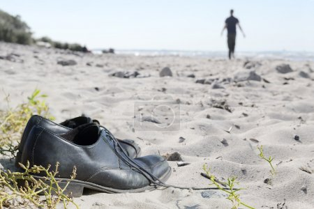 business shoes at the beach and a blurred man walking away to th
