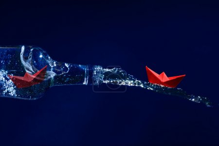 Red paper boats escape on a water splash from a bottle, dark blu