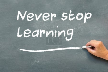 Photo for Older hand writing on a chalkboard the words never stop learning - Royalty Free Image