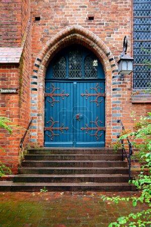 Photo pour Porte bleue en bois, entrée d'une vieille église en brique, typique du nord de l'Allemagne - image libre de droit